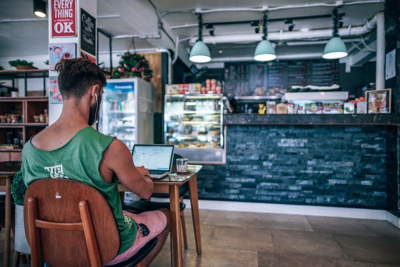 ein cafe mit einer schwarzen Bar, links sitz auf einem Holzstuhl ein junger Mann mit grünem t-Shirt und arbeitet an einem kleinem Laptop