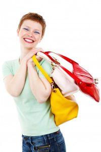 Junge Frau mit kurzen roten Haaren lächelt mit drei verschiedenen Taschen über der Schulter