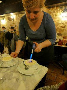 Katalanische Creme die im Restaurant von einer Dame am Tisch karamellisiert wird