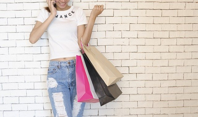 junge Frau vor einer weissen Backsteinwand, die lächelnd mit ihrem Handy telefoniert, und mit dem linken Arm drei Einkaufstüten hoch hält, sie hat ein weisses T-shirt und kaputt Jeans an
