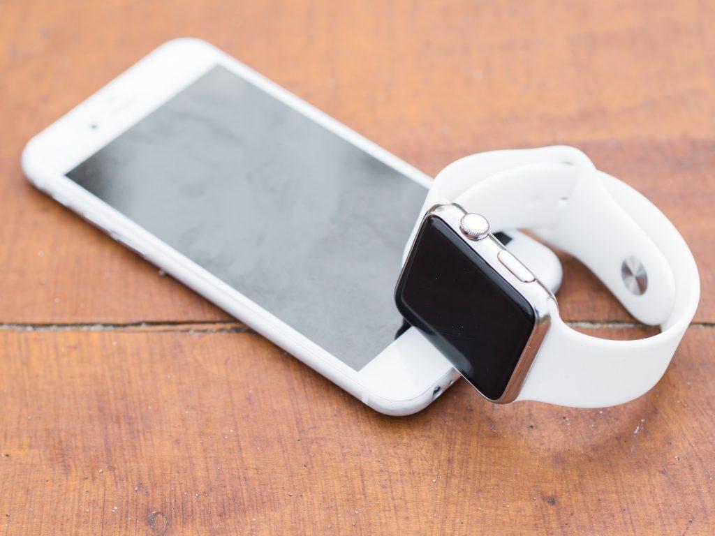 weißes iPhone und weiße Smartwatch die auf einem Holztisch liegen