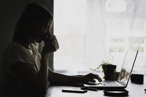 schwarz-weiss Foto von einer jungen Frau in hellem T-Shirt die gerade aus einer Tasse trinkt und mit der anderen Hand etwas am Laptop macht, auf dem Tisch ist auch ein Handy, die Untertasse und eine kleine spärliche Pflanze