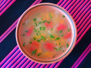 Quinoa Suppe i einer Schüssel auf einer Tischdecke in dunkel blau und knalligem rosa