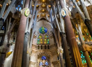Teil des Inneren der Sagrada Familia, zu sehen sind Säulen und mehrere bunte Fenster