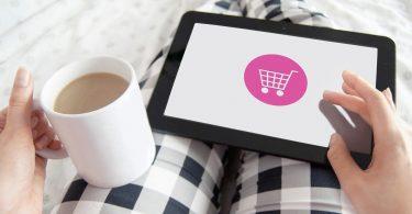 eine Person mit schwarz-weiß karierter Hose die mit im Bett liegt in der linken Hand eine Tasse Milchkaffee hält und mit der rechten Hand auf einem Tablet online shoppt
