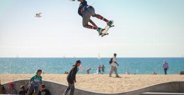 ein skate-platz am strand in dem drei skater fahren und springen