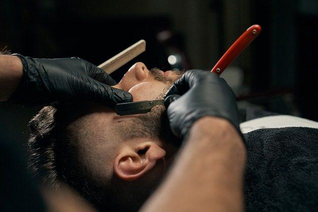 der kopf eines Mannes der auf einen Frisörstuhl liegt und sich von einem Barber rasieren lässt