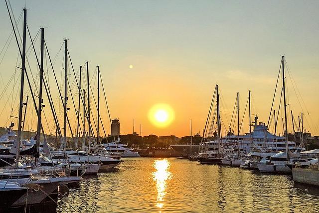 Hafen von Barcelona in der Mitte die untergehende Sonne und and den Seiten geparkte Schiffe