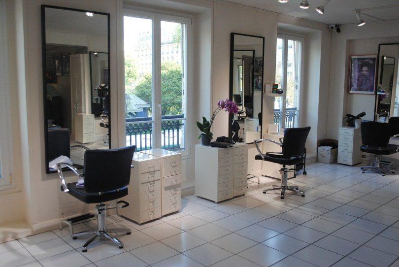 ein Friseursalon in weiß mit schwarzen Sesseln die vor spiegeln sehen mit einer kleinen weißen Kommode daneben und Fenstern dazwischen