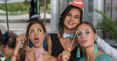 vier junge Frauen die verschieden assecoirs wie Brillen, Hütte oder Fliegen an einem Stock halten und für das Foto lächeln