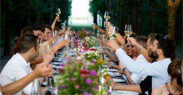eine langer gedeckter Tisch unter freiem Himmel an dem viele Leute sitzen die gerade ihr Glas zum anstoßen hoch heben