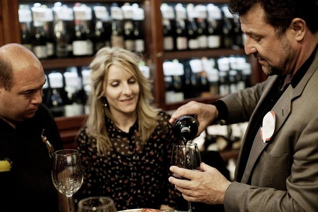 vor einem gefülltem Weinregal stehen ein glatzköpfiger Mann in schwarz, eine blonde Frau mit geblümter Bluse und ein Herr im grauen Anzug der den anderen beiden gerade Wein in ein Glas einschenkt