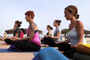 mehrere Frauen die sommerlich gekleidet am Strand auf Yogamatten sitzen und meditieren
