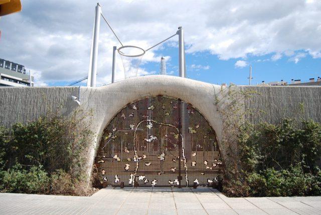 eine große halbrunde metalische eingangstür die in den Parc Central von Poblenou führt