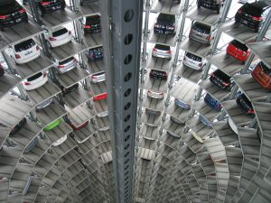 ein kreisförmiges Parkhaus von oben schräg rein schauend, man sieht fast alle Plätze sind besetzt