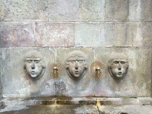 Frontaufnahme des Springbrunnens von Joan Fiveller, graue Steine und zwischen drei herausschauenden Köpfen sind zwei Bronze farbene Wasserhähne