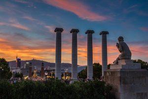 Die vier Säulen des Augustus Tempels bei Sonnenuntergang, davor ist eine weisse Statue zu sehen