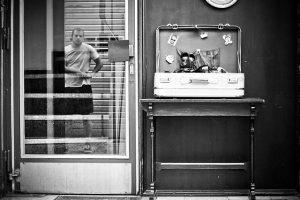 in der Glaseingangstür eines Ladens spiegel sich ein junger man in kurzen Hosen und t-Shirt wieder, rechts gegen der Tür steht ein rechteckiger Holztisch mit einem offenen alten Koffer darauf