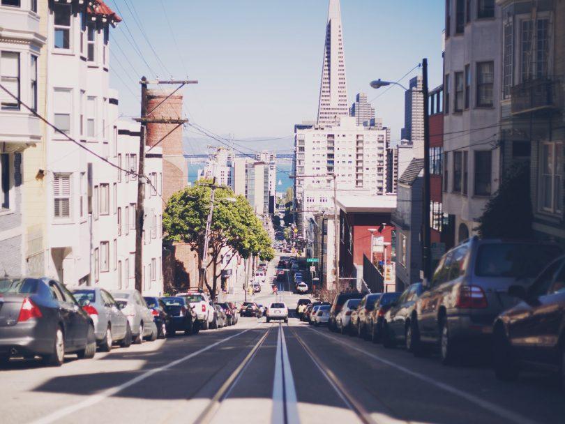 eine lange breite Straße die zwischen Wohnblöcken bergab bis zum Meer reicht, auf beiden Seiten sind Autos geparkt