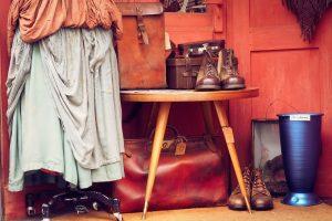 Schaufenster eines Second-Hand Ladens, ein kleiner Holztisch mit braunen Schuhen und mehreren braunen Taschen darauf, rechts daneben auf dem Boden braune Stiefel und eine blau metallische große Vase und links vom Tisch ein Ständer mit einem Rock und einem orangenen Tuch