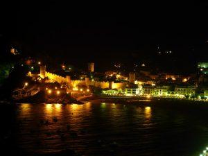Das Dorf Tossa de Mar bei nacht vom Meer aus fotografiert, man sieht die Promenade und die Burganlage beleuchtet