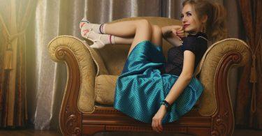 eine junge blonde Frau die auf einem grossen Sessel sitzt mit den Füßen auf der Lehne, sie trägt einen türquis glänzenden knielangen Rock, eine schwarze kurzärmlige Bluse weisse Stöckelschuhe und weisse Sportsocken