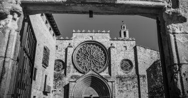 schwarz-weiss Bild der Sant Cugat Kirche, quadratische Gebäude und in der Mitte ist ein rundes verziertes Fenster
