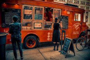 ein rötlicher Foodtuck mit vielen Tafeln auf der mit weisser Kreide alle Gerichte aufgelistet sind, eine junge Frau im schwarzen Kleid gibt gerade eine Bestellung auf und eine andere schaut sich das Menu an