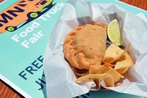 eine Pastete mit chips und einem Stück Limette in einem Take-A-Way Papier und darunter liegt ein Flyer einer Food Truck Messe