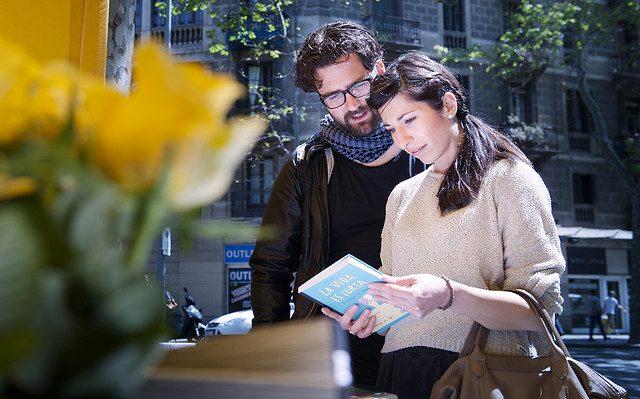 ein junges Pärchen das einem Bücherstand in Barcelona steht, sie sehen sich gerade ein Buch an