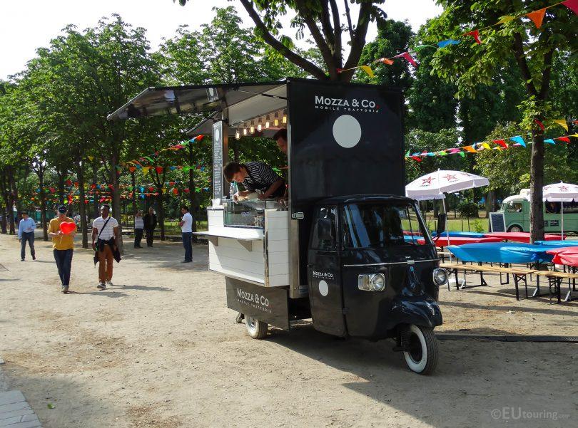 ein schwarzer Mini-Food-Truck der in einem Park steht