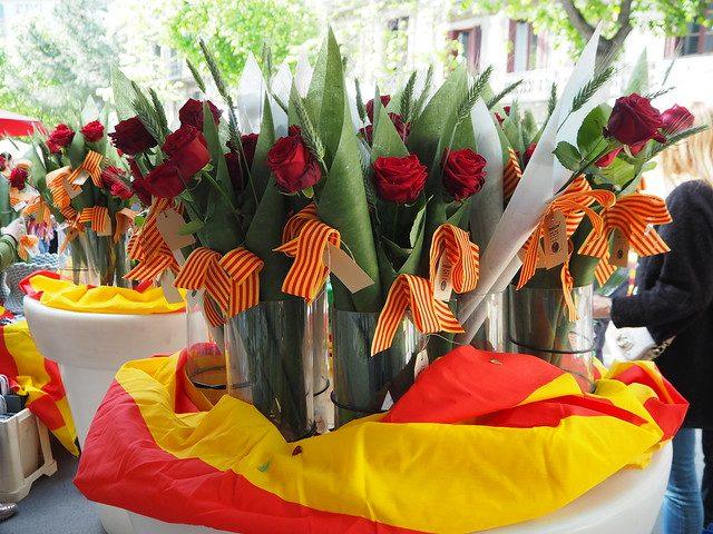 ein Tisch mit der katalanischen Flagge als Tischdecke und vielen roten Rosen darauf an einem Blumenstand zu Sant Jordi in Barcelona