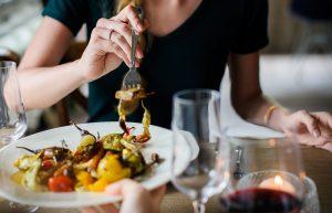ein Frau im schwarzen t-shirt die mit einer Gabel von einem Gemüseteller isst
