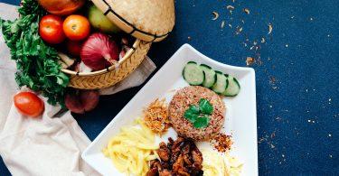 ein blauer Tisch mit einem Körbchen voller Gemüse und einem rechteckigen Teller mit nudeln Gurkenscheiben und Fleisch