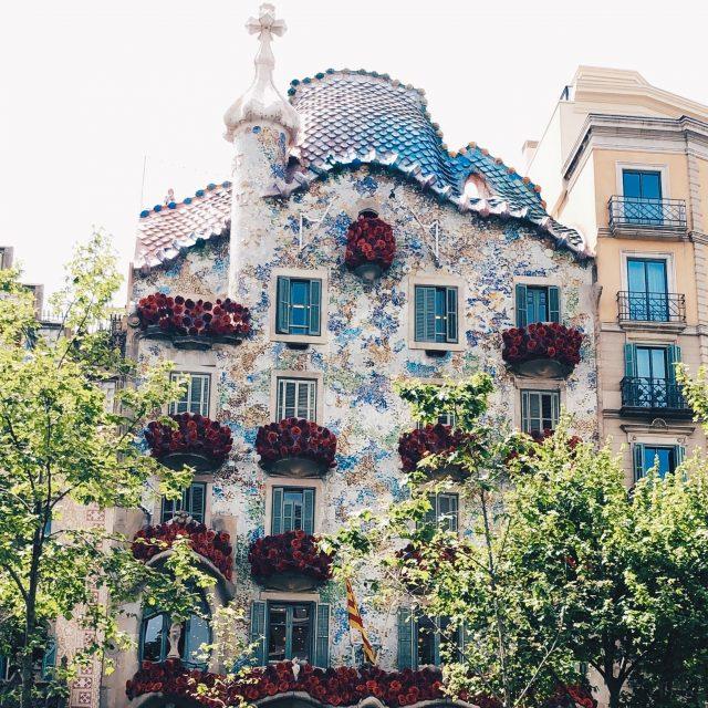 ein Gebäude des Architekten Gaudi in Barcelona, das alle Fenster und Balkone mit roten Rosen geschmückt hat