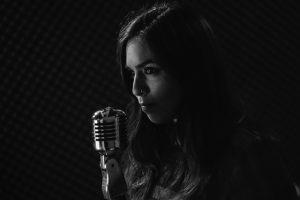 schwarz-weiss Foto eines Frau mit Nasenring und langen Haaren vor einem Vintage Mikrofon