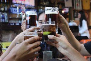 fünf Freunde stossen mit Bier und Cocktail an , man sieht nur die Getränke und Hände und Teil des Gesichts einer Frau