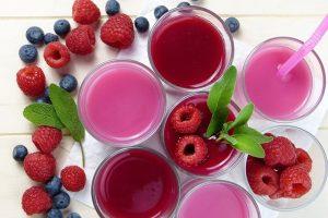 weisser Tisch mit einigen Gläsern mit Fruchtsäften und drum herum Himbeeren und Blaubeeren und Minzblätter