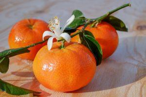 drei Mandarinen auf einem Holztisch mit Blättern und einer Blüte