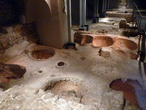 das Untergeschoss des MUHBA, ein Steinboden mit mehreren grossen Löchern