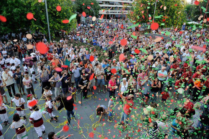 Platz mit vielen tanzenden Menschen Luftschlangen und Ballons