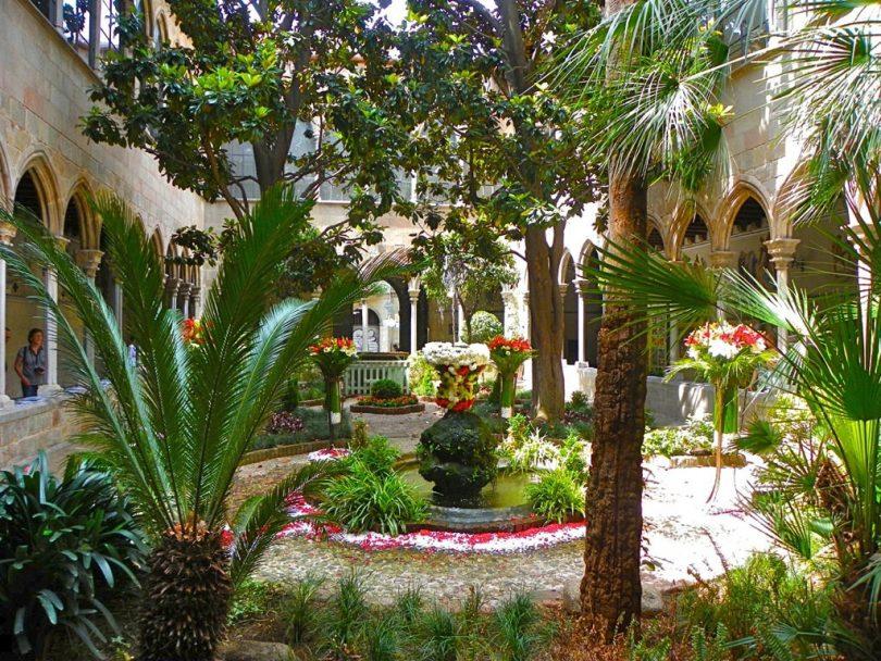 der Innenhof einer Kathedrale mit einem Blumengeschmückten kleinen Springbrunnen in der Mitte