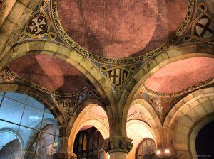 Saal mit mehreren Säulen und gewölbter Decke und in den Ecken verschiedenen Wappenzeichen