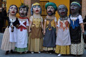 sechs Dickköpfe, ein Bauernpärchen, ein Adelspärchen und ein farbiges Pärchen, wobei alle Herren lange Kleider mit Schütze tragen