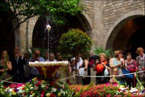 eine Menschenmenge die um einen Springbrunnen im Vorhof einer Kirche steht und ein weißes Ei auf seinem Wasserstrahl tanzen lässt, drum herum ist alles mit Blumen geschmückt