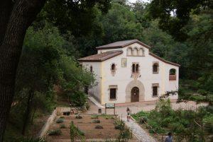 ein älteres Bauernhaus das mitten im botanischen Garten steht, es ist weiss gestrichen und hat unten zwei groe eckige Fenster und oben mehrere kleine gewölbte Fenster