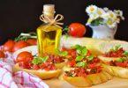 ein Tisch mit sechs Tomatenbroten, eine kleine Flasche mit Olivenöl und im Hintergrund ein angeschnittenes Baguette, Tomaten und eine Vase mit Gänseblümchen