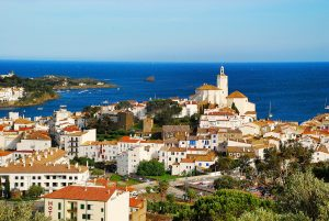 Das Dorf Cadaques vom Landesinneren Richtung Meer fotografiert, hellblauer Himmel und dunkel blaues Meer