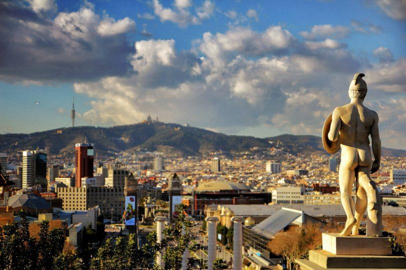 Aussicht auf Barcelona von Montjuïc aus, man sieht eine der Statuen des Nationalmuseums und ein blauer Himmel mit einigen weißen Wolken