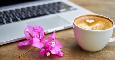 Bogambillablüten zwischen einem Milchkaffe mit Herzmuster im Schaum und man sieht einen Teil eines Laptops auf einem Holztisch